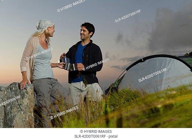 Couple having tea at campsite