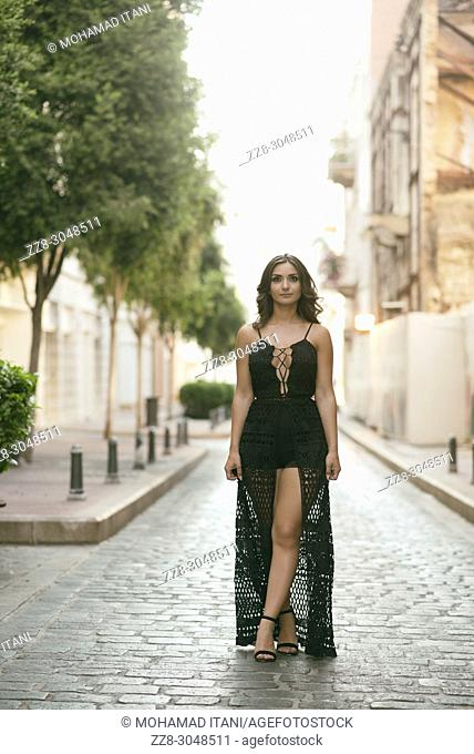 Beautiful young woman swearing a sexy dress walking on a cobbled road