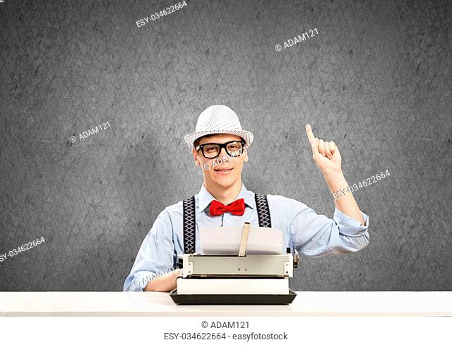 Young guy writer in hat and glasses using typing machine