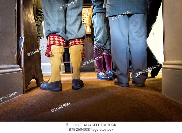 Close-up of the feet of hunters, wearing typical shoes and socks, in a pub. Yorkshire, England, UK, Europe