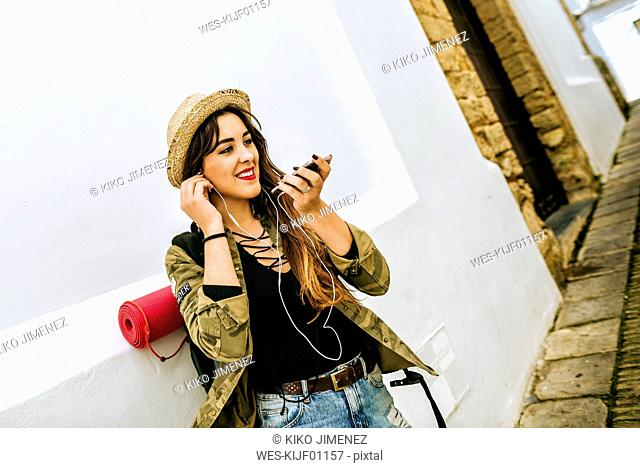 Smiling young traveling woman using cell phone