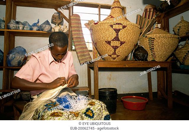 Refugee making traditional woven baskets