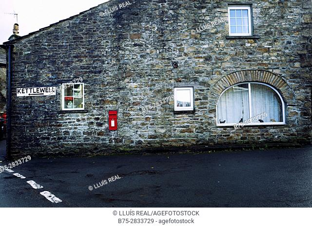 """Stone house facade with windows, mailbox and a sign reading """"Kettlewell"""". Gayle, Hawes, North Yorkshire, Yorkshire Dales, Skipton, UK"""