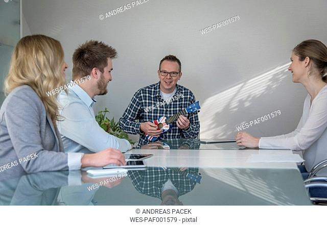 Colleagues having a meeting with man playing banjo