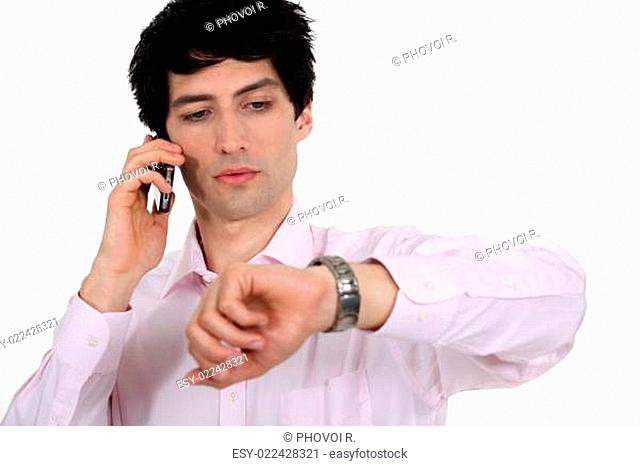 Businessman looking at his watch while taking a call