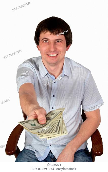 Man in shirt with short sleeves sitting in a chair and holds up to the camera money isolated on white background