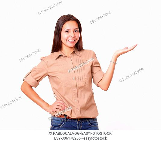 Portrait of 20s beautiful girl holding up her left palm while standing and smiling at you on isolated white background - copy space