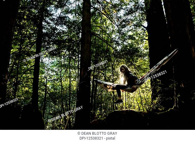 A woman sits in a hammock in a forest at sunset; Arizona, United States of America