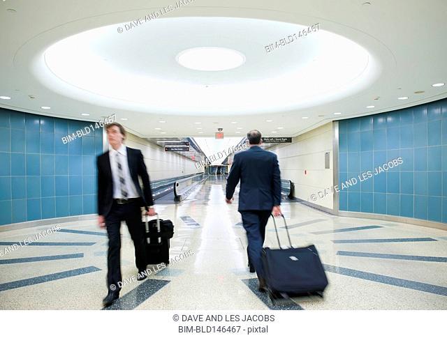 Caucasian businessmen pulling luggage in airport