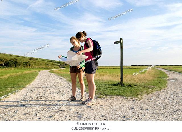Female hikers check route on map