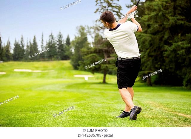 A male golfer driving a golf ball down the fairway of a golf course with the ball in mid-air; Edmonton, Alberta, Canada