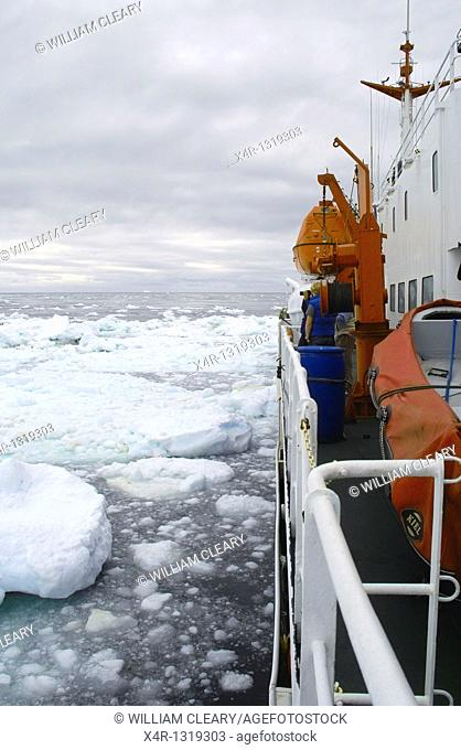 View to starboard side and aft of the Antarctic cruise ship MV Ushuaia as she pushes slowly through an area of heavy ice floes, also known as growlers