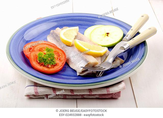 fresh herring with lemon slice, apple, tomato and parsley on a plate