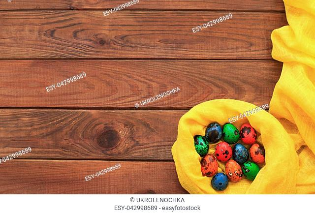Easter background with colorful painted quail Easter eggs on wood background in a nest and yellow fabric border. Copy space, vintage style, top view