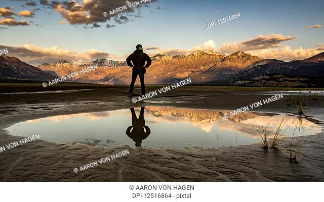 A man stands with his reflection in a pool of water looking out over the Saint Elias Mountains at sunset, Kluane National Park and Reserve; Destruction Bay