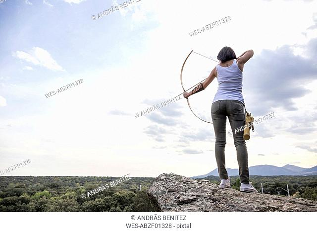 Archeress standing on a rock aiming with bow