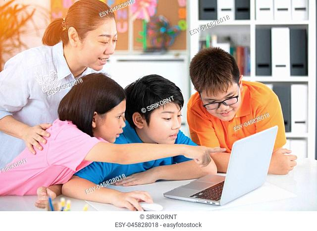 Asian woman teacher and Cute Asian children using laptop computer together