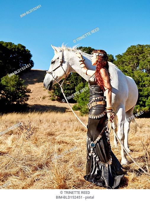 Nomadic Caucasian woman walking horse in field