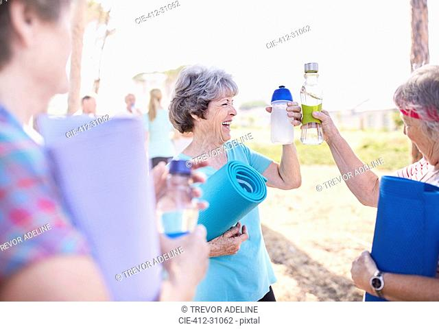 Senior women toasting water bottles after yoga class in park