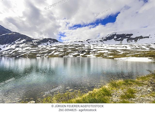 mountain lake Djupvatnet with snow, Norway, below mountain Dalsnibba near Geiranger