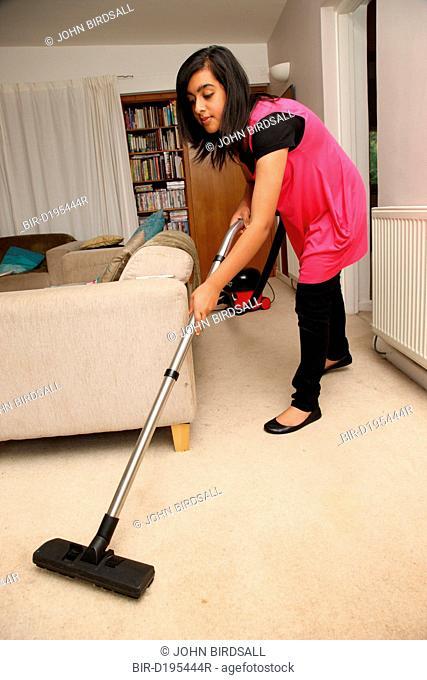 Teenage girl hoovering a carpet