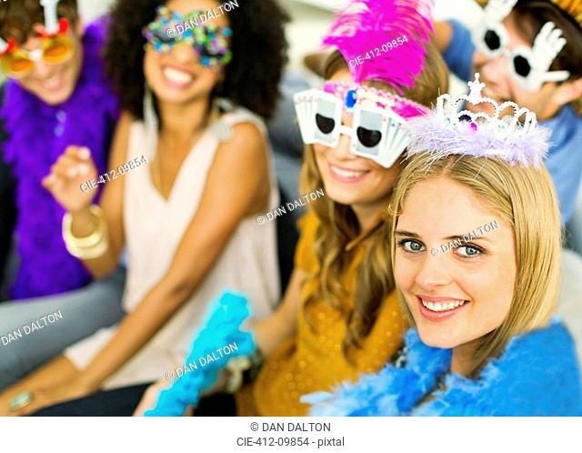 Friends wearing decorative glasses and crowns at party
