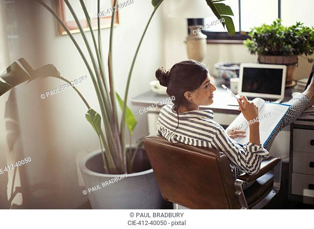 Businesswoman reading paperwork with feet up on desk