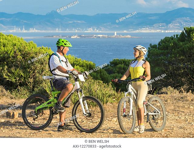 A man and woman on bicycles stand with a view of the ocean and coastline; Tarifa, Cadiz, Andalusia, Spain
