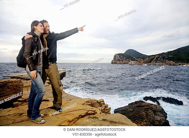 Excursionist couple in a cliff by the sea