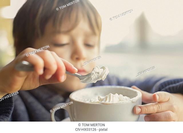 Close up boy scooping and eating whipped cream off hot cocoa
