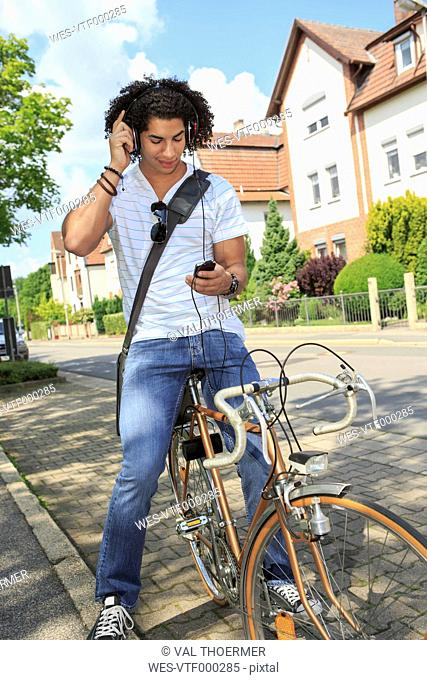 Young male student with headphones sitting on a bicycle looking at his smartphone