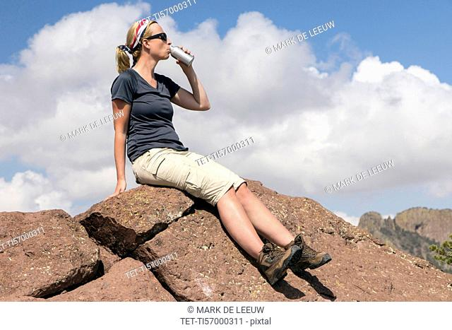 Woman sitting on rock and drinking from bottle