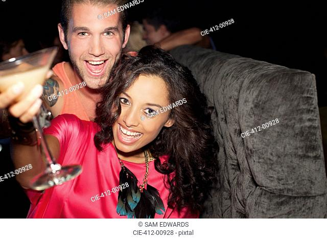 Portrait of enthusiastic couple drinking cocktail in nightclub