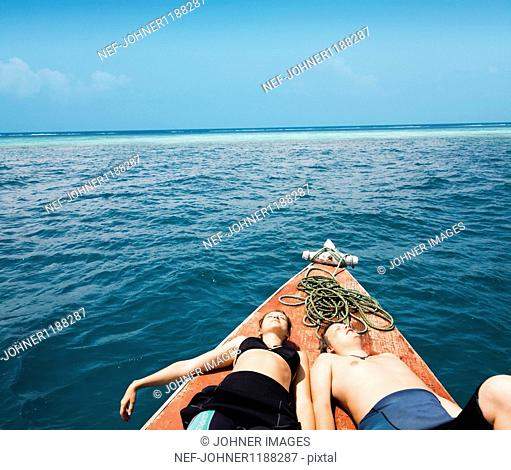 Couple sunbathing on deck of boat
