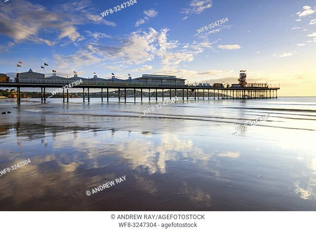 Clouds patterns over Paignton Pleasure Pier on the south coast of Devon reflected in the wet sand on the beach