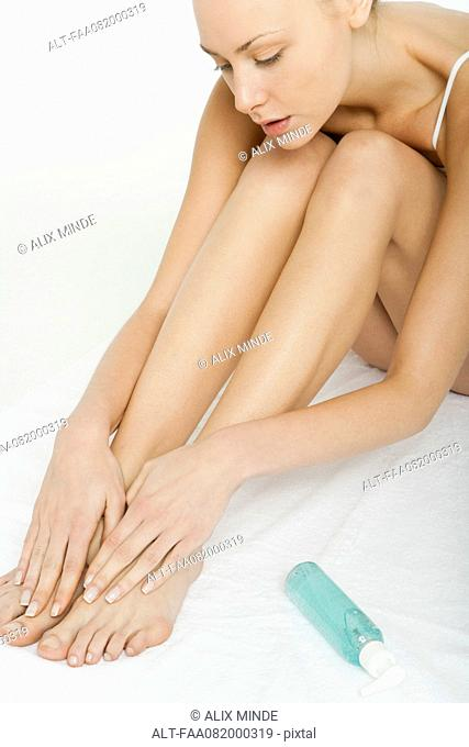 Young woman moisturizing bare legs