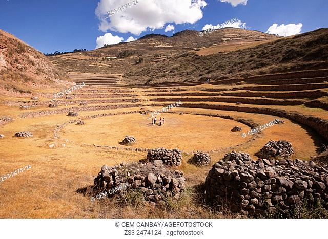 Tourist during a meditation session in the middle of the terraces at the Moray Ruins of the Inca empire, Cusco Region, Peru, South America