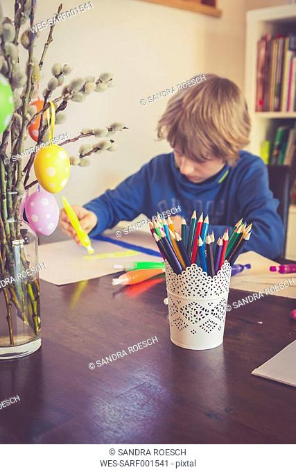 Boy painting with Easter decoration in foreground