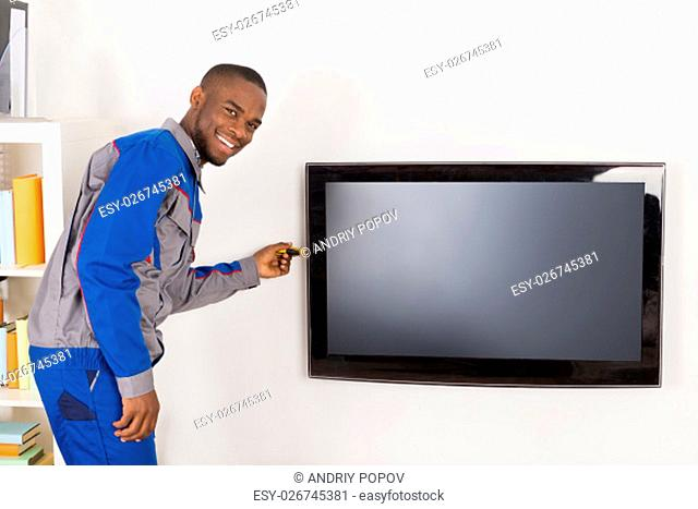 Male African Technician Repairing Television Mounted On Wall