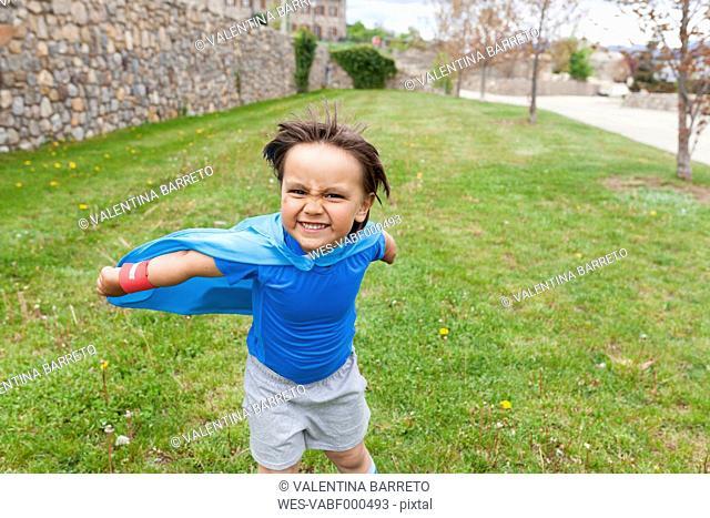 Little big hero posing on meadow