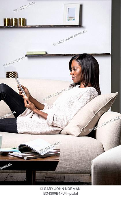 Young woman relaxing on sofa, using digital tablet