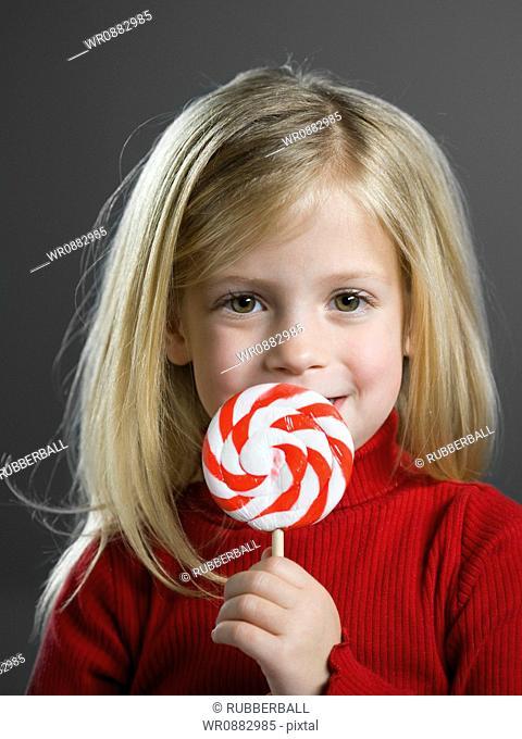 Portrait of a girl holding a lollipop