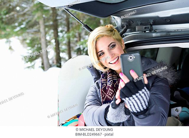 Caucasian woman at car posing for cell phone selfie in winter