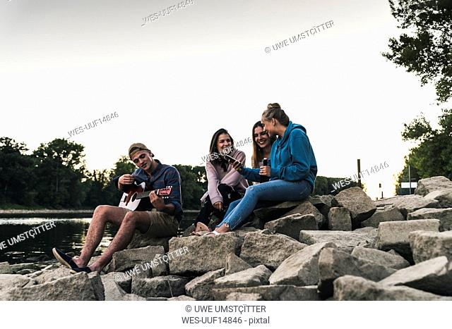 Group of friends sitting at the riverside in the evening