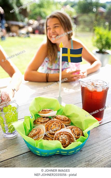 Cinnamons buns with Swedish flag, girl on background