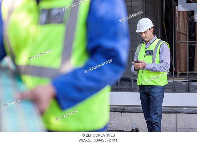 Men with cell phone on construction site