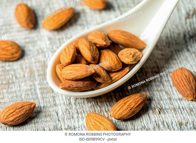 Almond nuts on serving spoon and on background