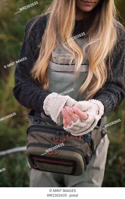 A woman with long blonde hair putting on woollen fingerless mittens
