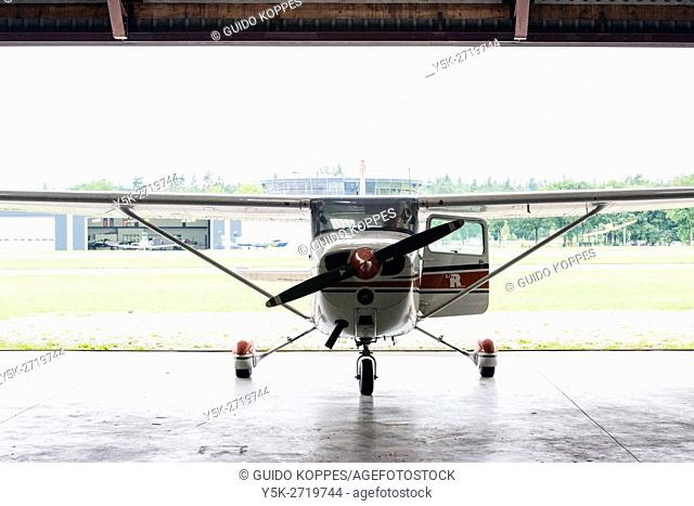 Seppe Airfield, Oudenbosch, Netherlands. A small Cessna four seat airplane parked in the Hangar doors of an airfield
