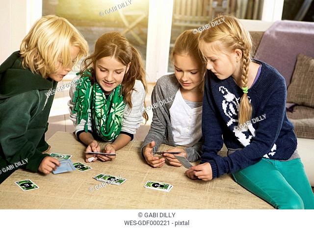 Four children playing card game in living room
